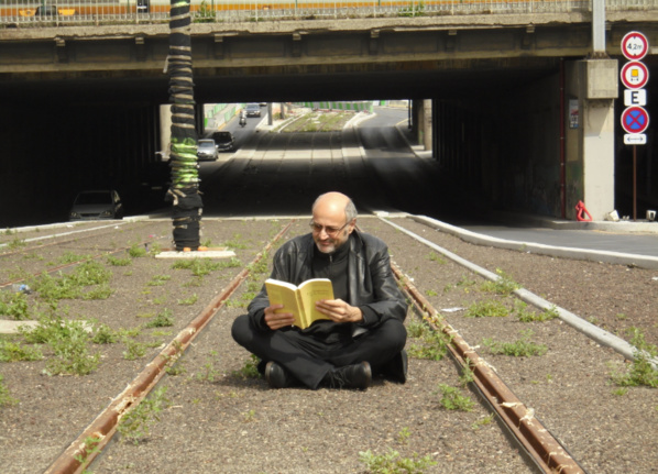 Lire Partout!: Pierre Martial lisant au beau milieu des boulevard des Maréchaux à Paris, entre les rails du tramway