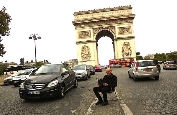 Pierre Martial lisant au beau milieu des Champs-Elysées à Paris
